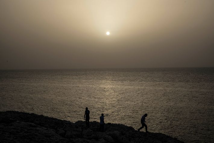 People watch the strange-colored sunset, tinged by the cloud of Saharan dust hanging in the air, ...