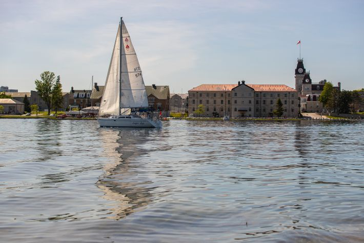 This yacht is sailing on the St. Lawrence River with downtown Kingston in the background.