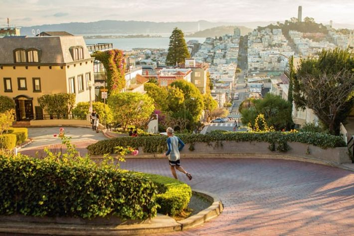 A man jogs down Lombard Street in the early morning.
