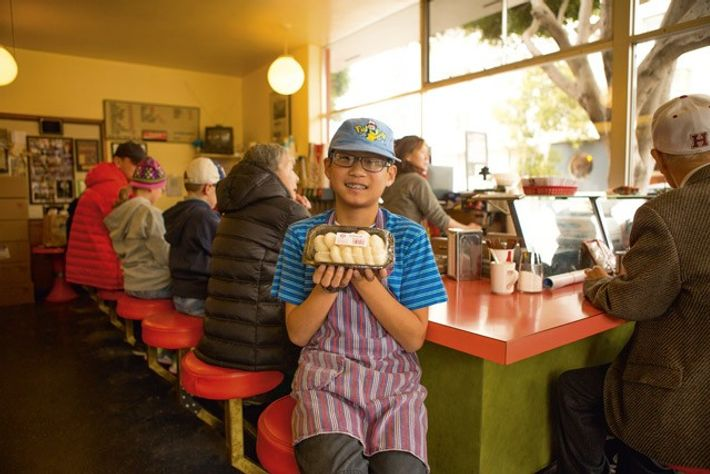Hiroki Matsuno holds up traditional mochi at benkyodo in Japantown.