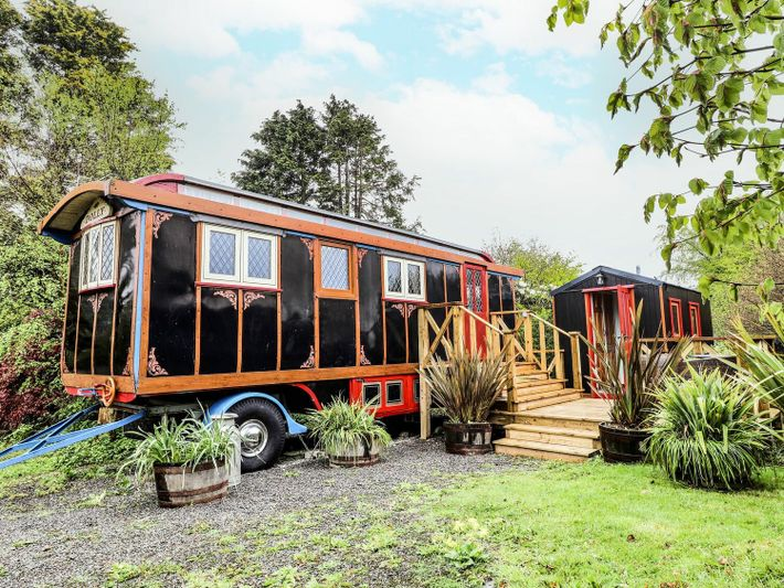 The spacious quarters ofCeredigion'sDolly the Circus Wagon include theatrical drapes in the bedroom, vintage seating and ...