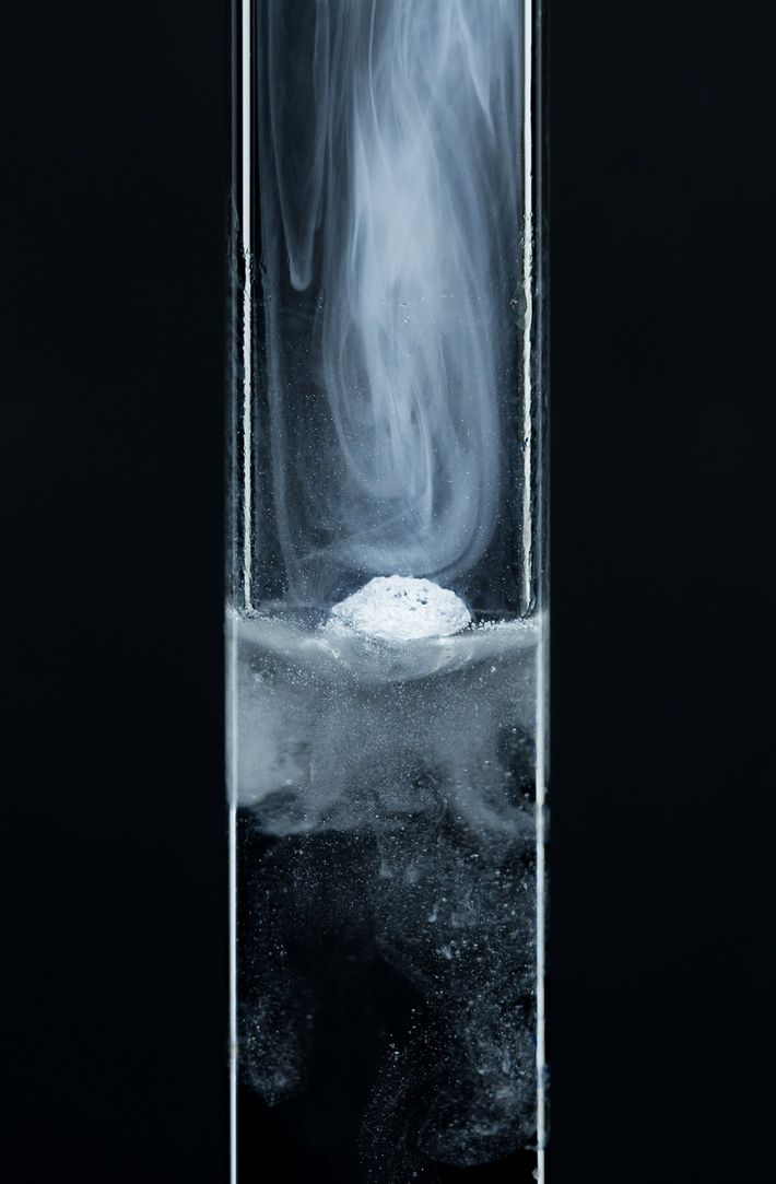 As a small particle of potassium metal is dropped into a test tube of water, it ...