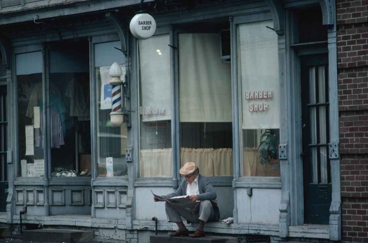 Whilst waiting for opening time, a man reads a newspaper on the front stoop of a barbershop ...