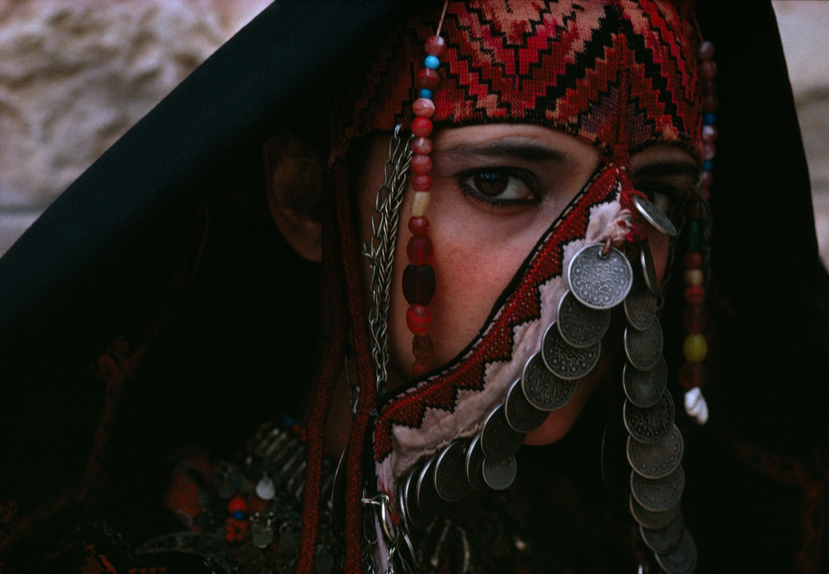 A young woman in Amman, Jordan, models traditional Palestinian dress. This picture appeared in a June ...