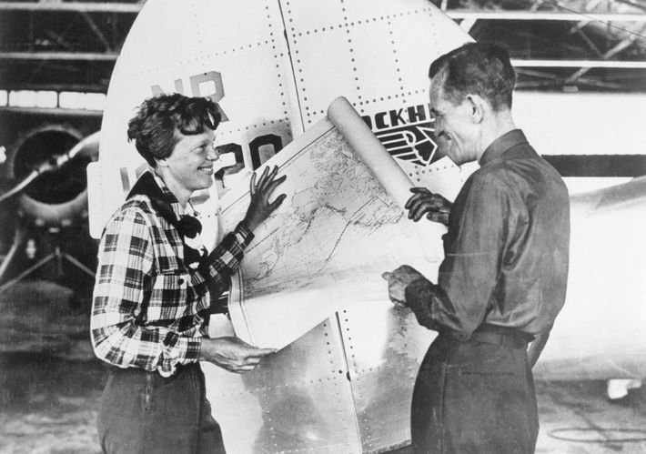 Earhart and navigator Fred Noonan consult a map of the Pacific that shows the planned route ...