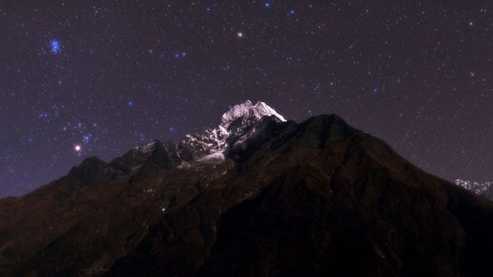 The bright star Aldebaran in the constellation Taurus peeks over Mount Thamserku in Nepal.