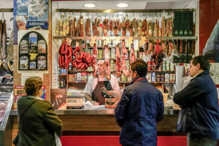 A butcher's stall hung with legs of jamón at Mercado de Triana.