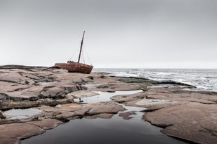 The rusty remains of the shipwrecked Brion cargo vessel can be seen on the rocky shore ...