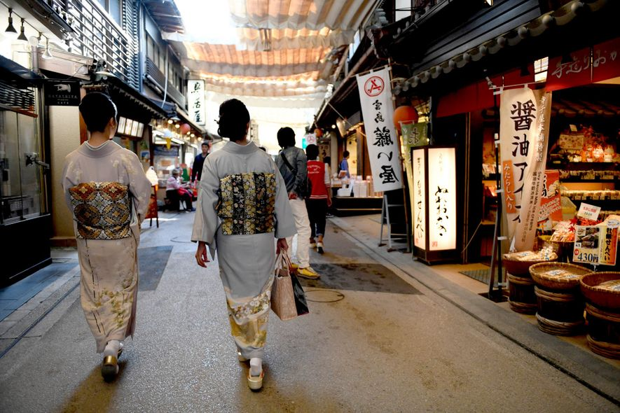 Two women wander the Omotesando Shopping Arcade on Miyajima.