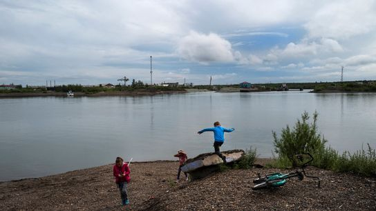 Children play on the banks of the Kolyma River in the Siberian town of Zyryanka, Russia ...