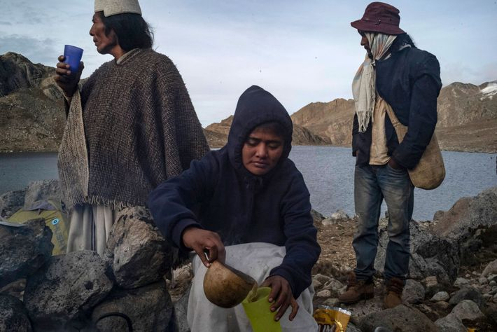 Gladys Martínez (center) makes warming coffee with powdered milk for Eulogio Villafaña (left) and Ever Maestre ...