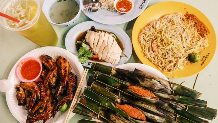 A feast at a Singapore hawker center might include (clockwise from left): barbecue chicken wings with ...