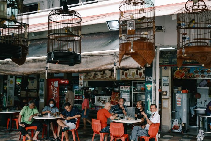 Customers sit at a kopitiam (coffeehouse) in a hawker center next to the Kebun Baru Birdsinging ...