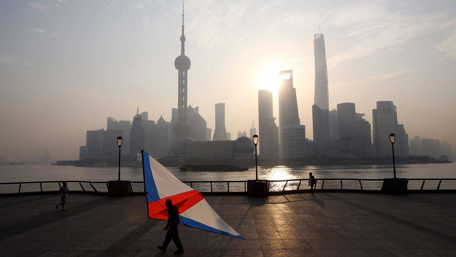 A man carries a large kite at sunrise in front of the distinctive skyline of Pudong, ...