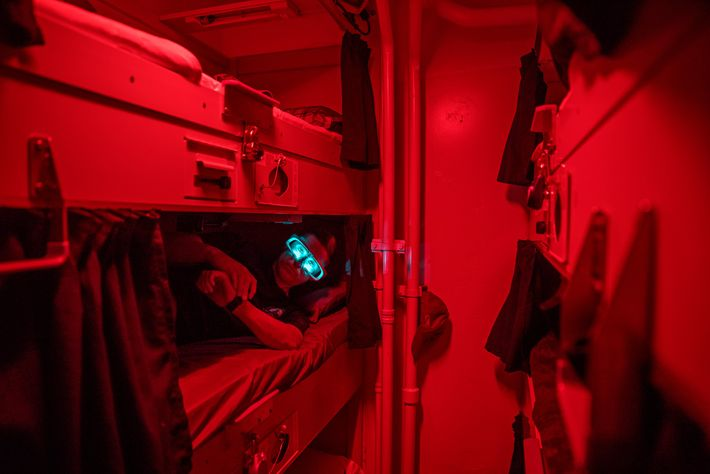 Resting in his bunk on the U.S.S. Paul Hamilton, a sailor wears light-emitting goggles for a ...