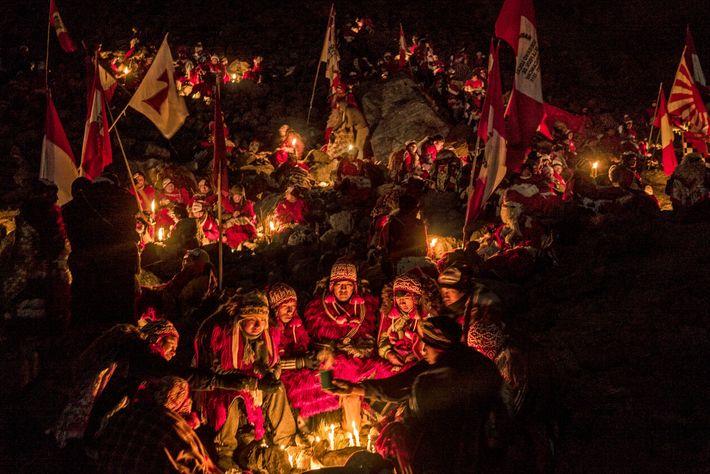 Huddling around candles before dawn, men from Peru's Quispicanchi nation celebrate Qoyllur Riti below a glacier. ...