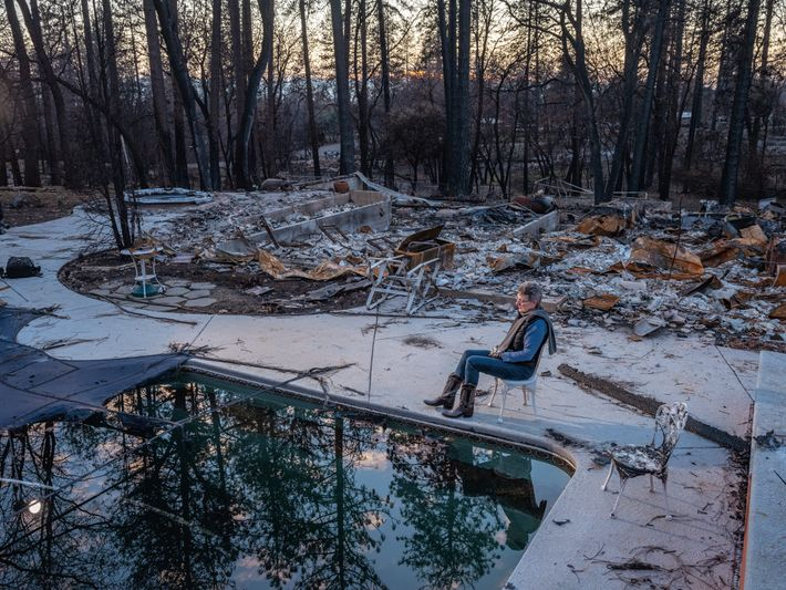 Gwen Nordgren sits for a portrait by the pool next to the charred ruins of her ...