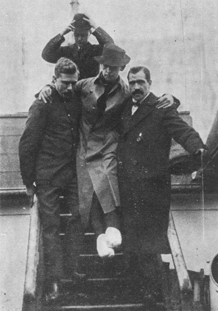 Rescuers from Carpathia help Titanic's radio operator Harold Bride disembark in April 1912.