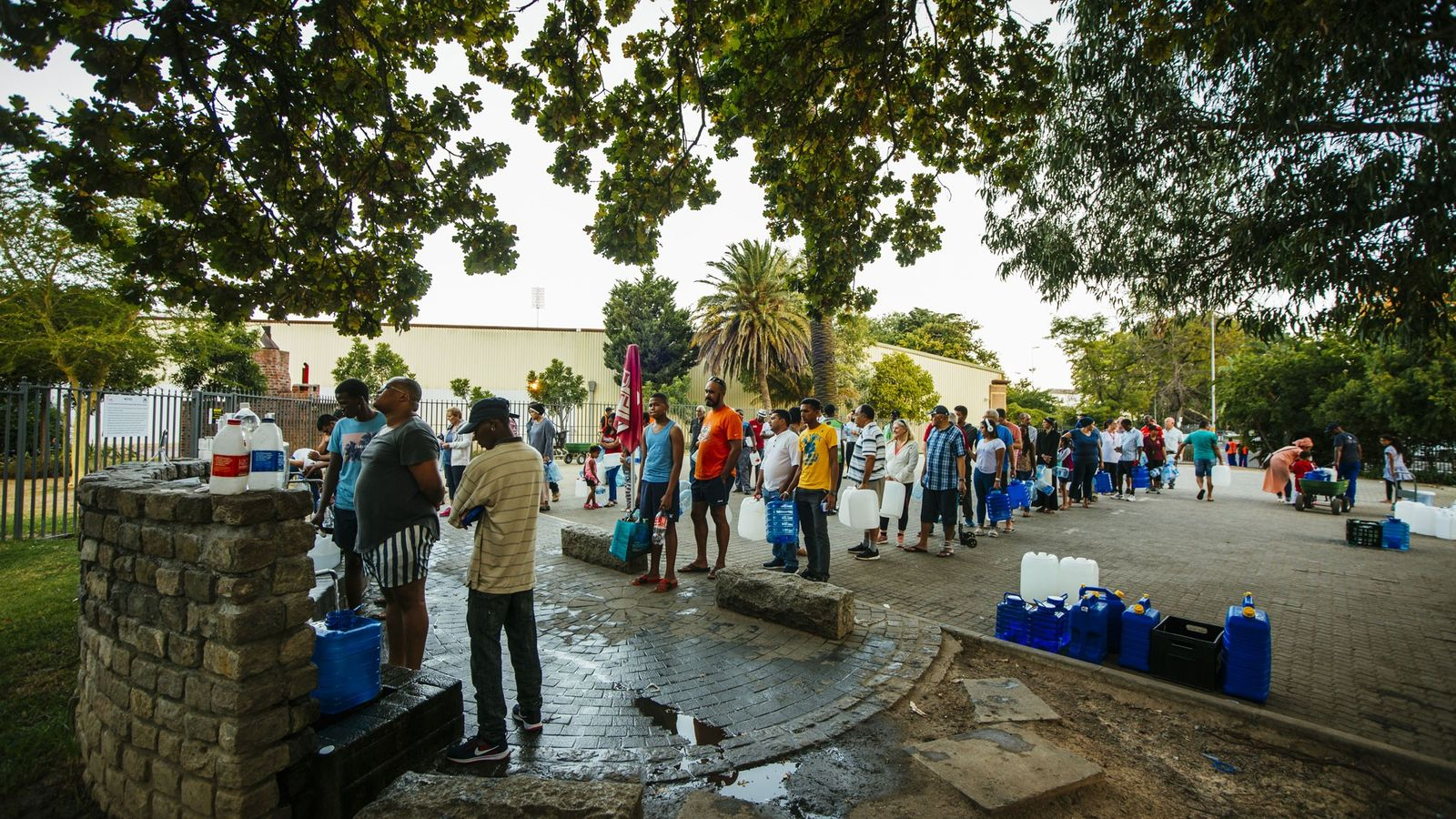 Residents queue to fill water bottles at a natural water spring in Cape Town, South Africa, ...