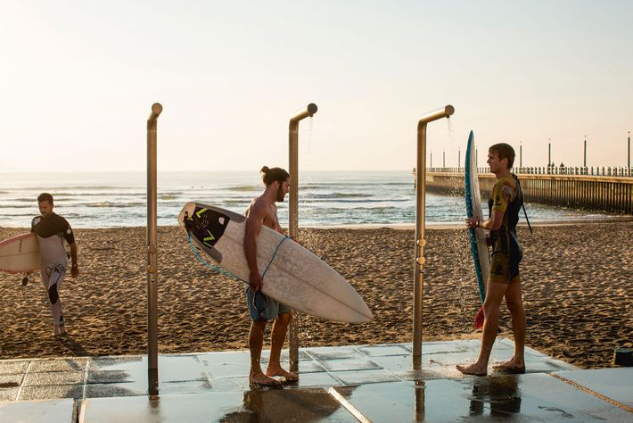 Cleaning surfboards on Durban's Golden Mile.