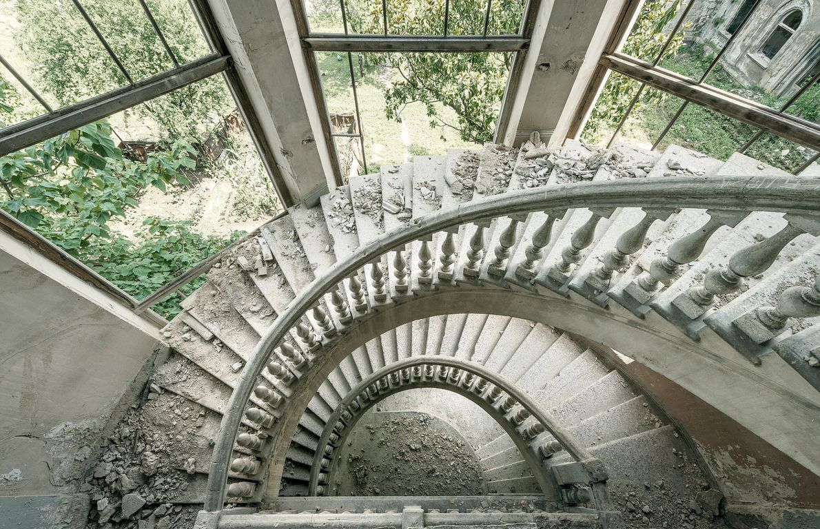 Nature encroaches on this crumbling spiral staircase.