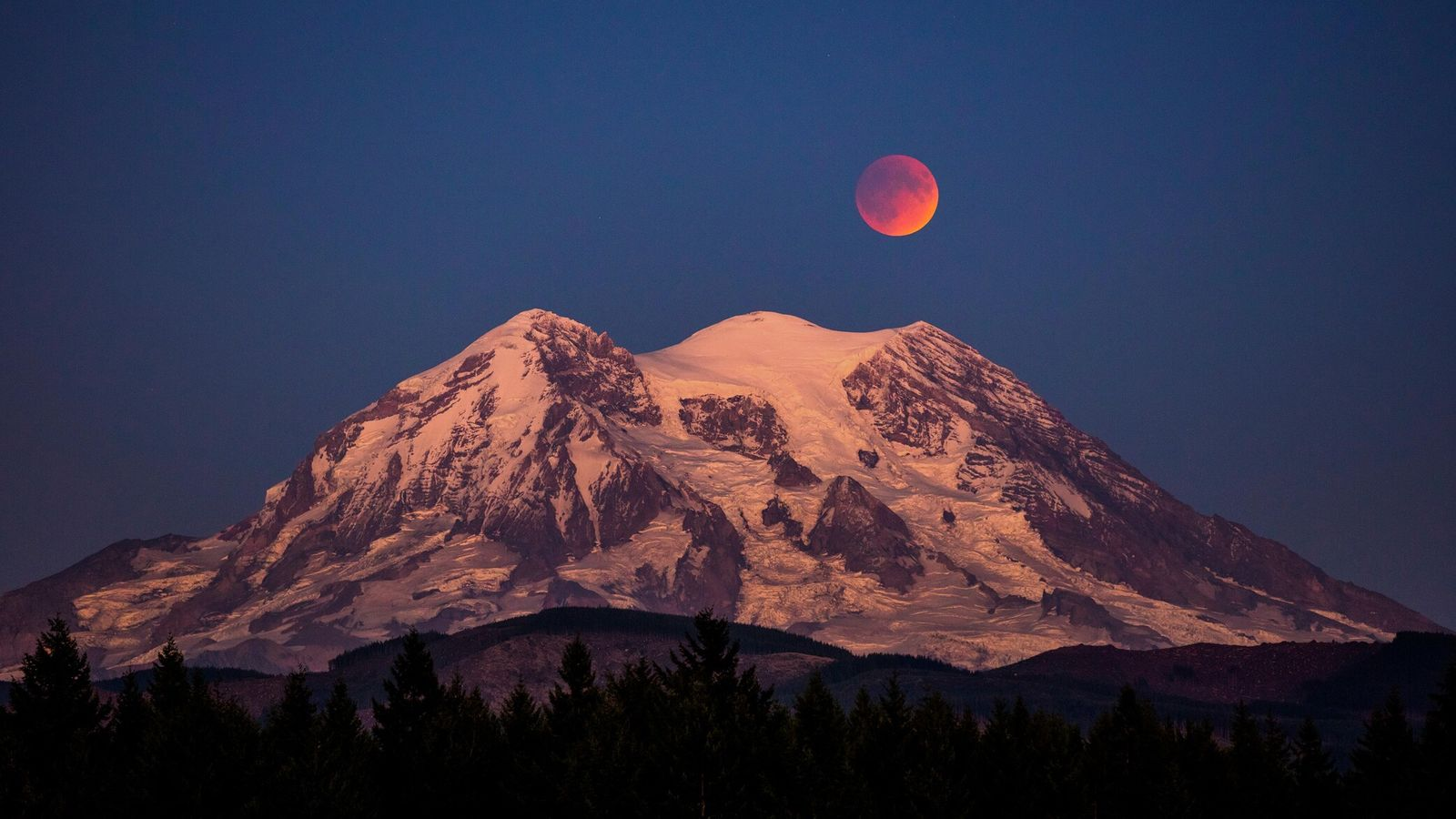 A blood moon, an evocative nickname for a total lunar eclipse, hangs over Mount Rainier in ...