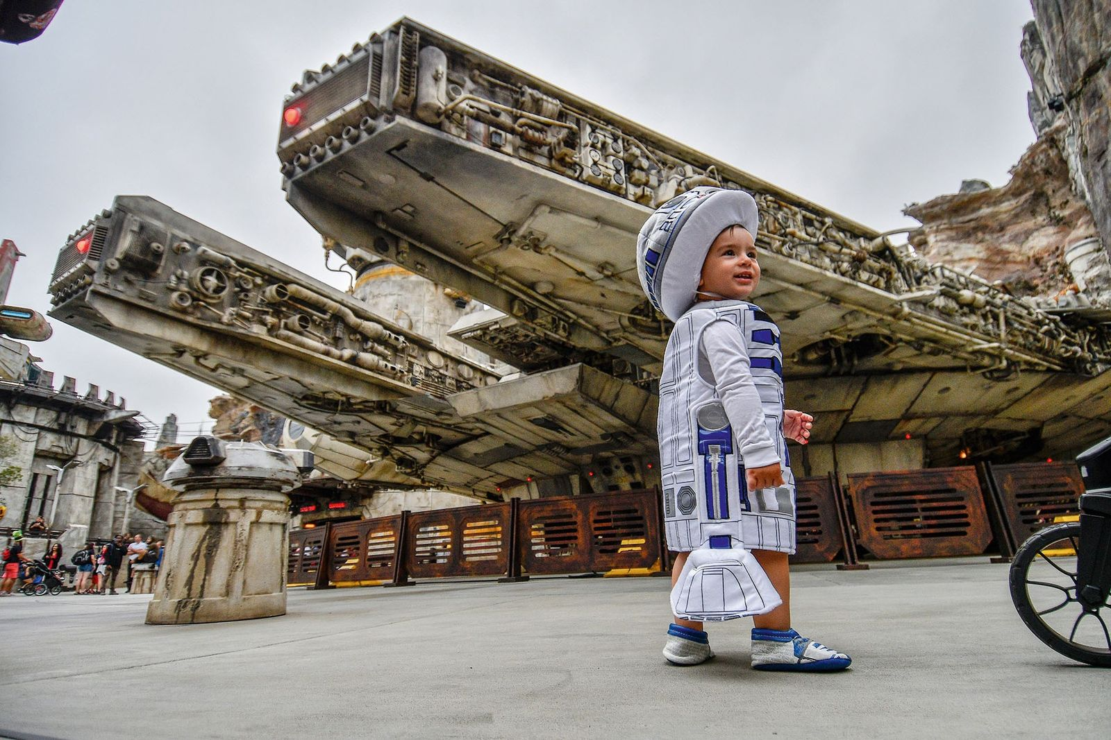 A young fan in a R2D2 costume stands outside a replica of the Millennium Falcon.