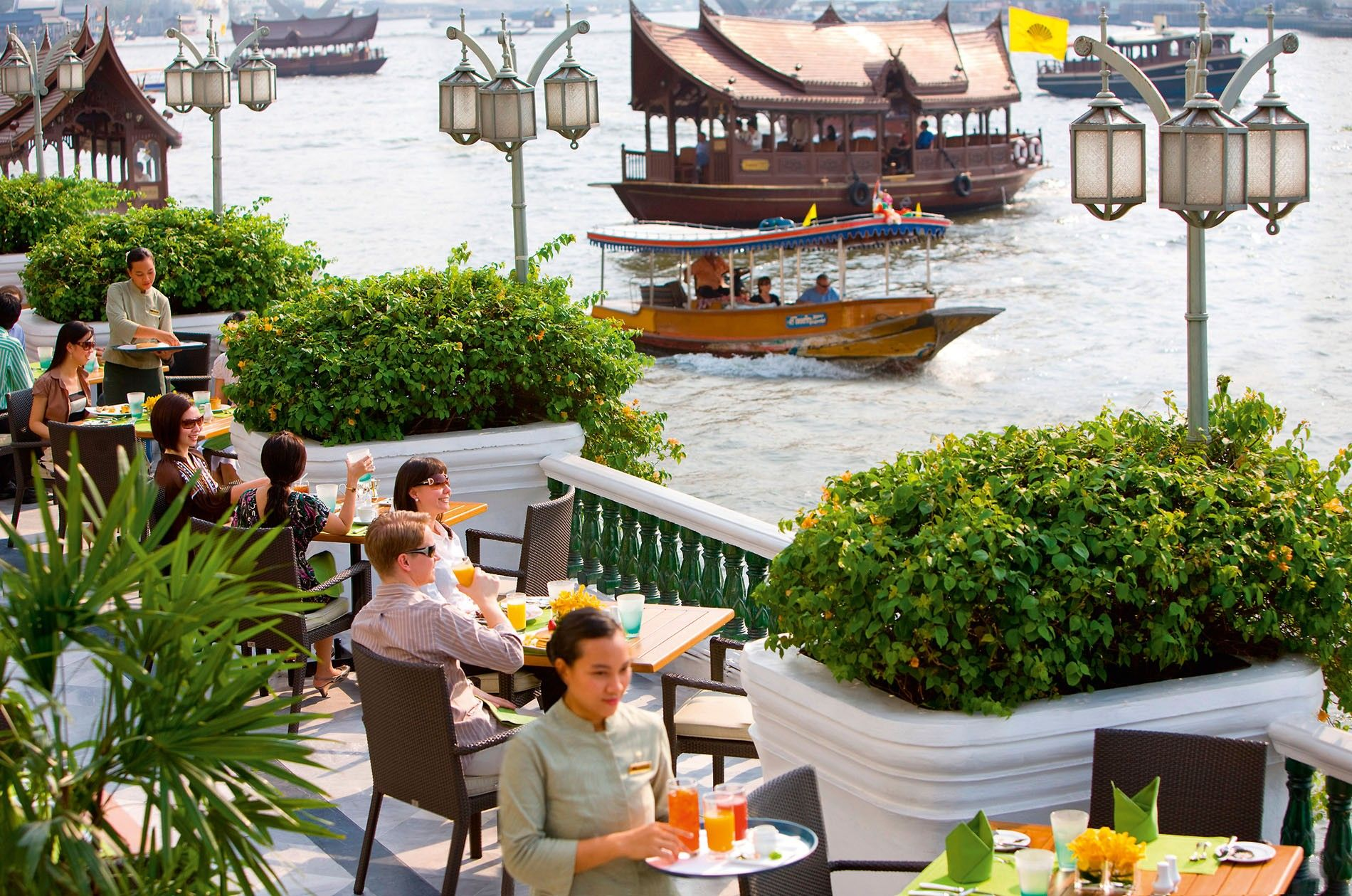 Diners on a terrace beside Chao Phraya River