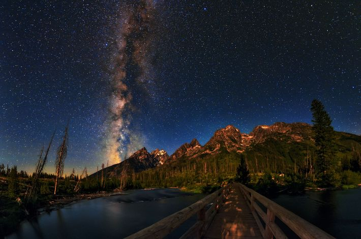 The Milky Way glows over the Rocky Mountain range in Grand Teton National Park.