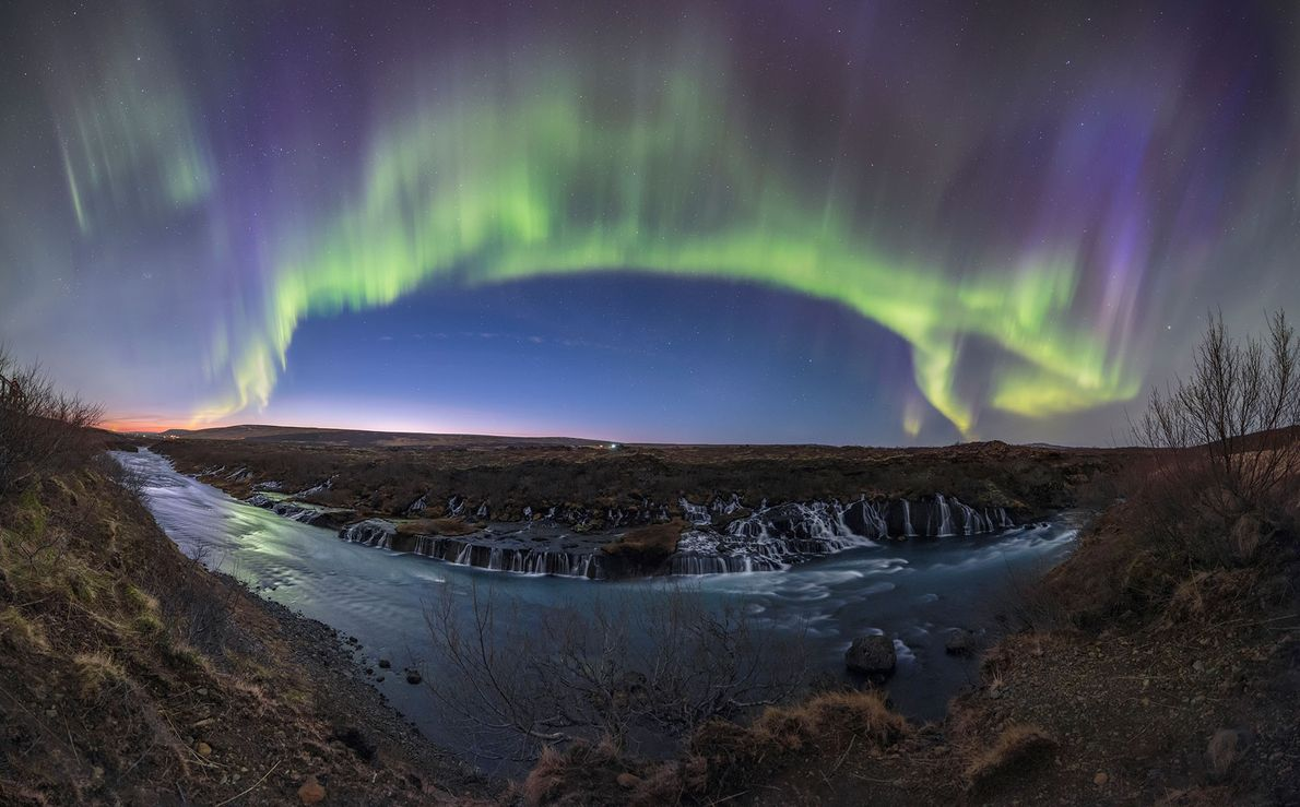 A green and purple aurora display dominates the sky above the waterfalls along the Hvita river ...