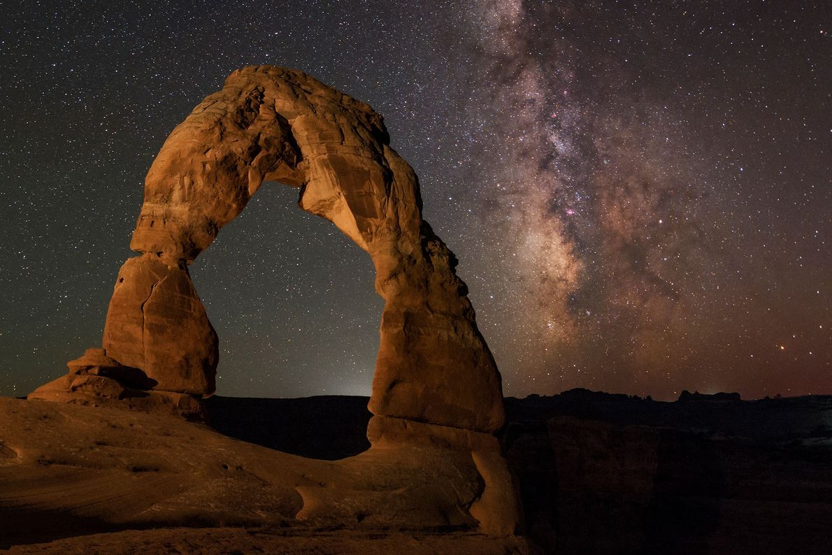 The Milky Way can be seen behind a delicate rock formation in Arches National Park.