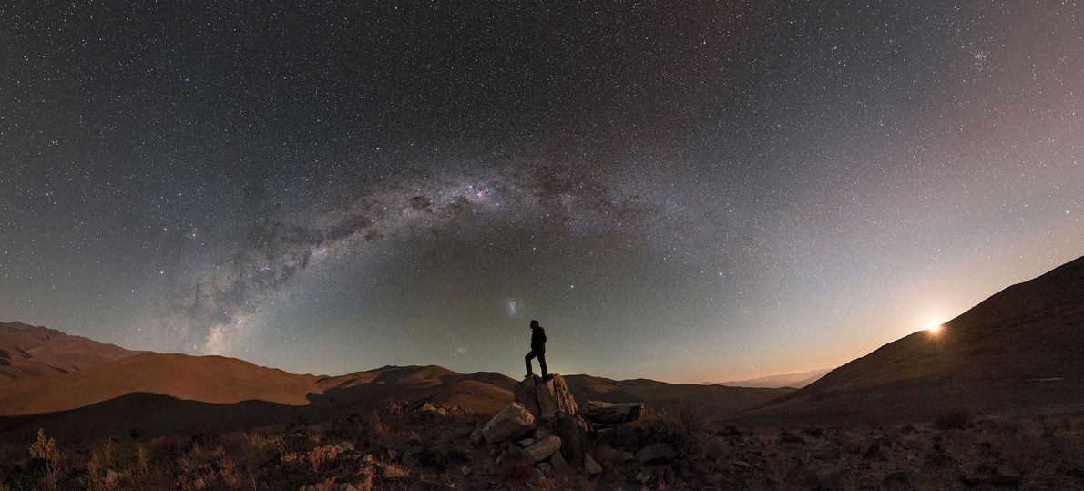 As the moon sets in the desert, the stars and Milky Way are still visible.