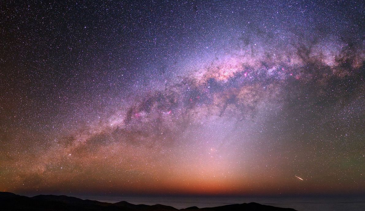 Among a colourful night sky and bulging Milky Way a satellite flare can be seen on ...