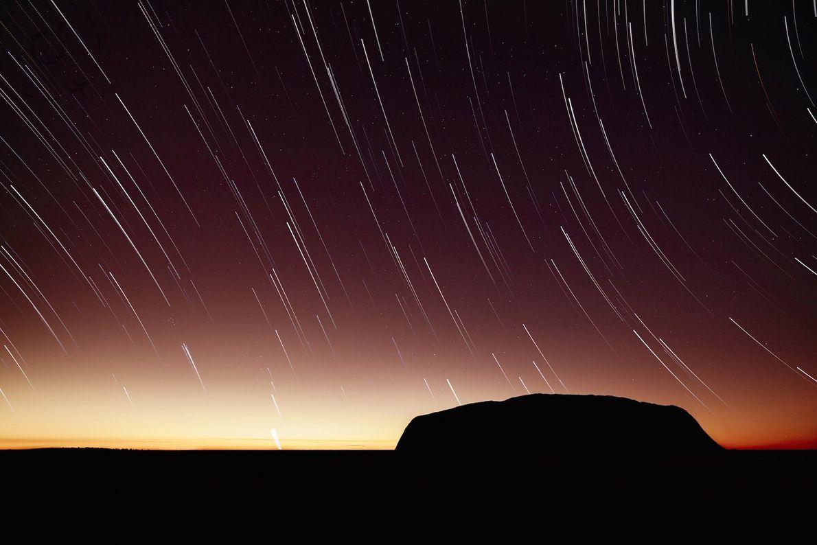 A long exposure at sunrise shows star trails wheeling above Uluru.