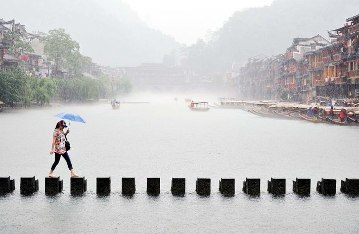 A woman crosses this stepping stone bridge on a rainy day in Phoenix Ancient Town.