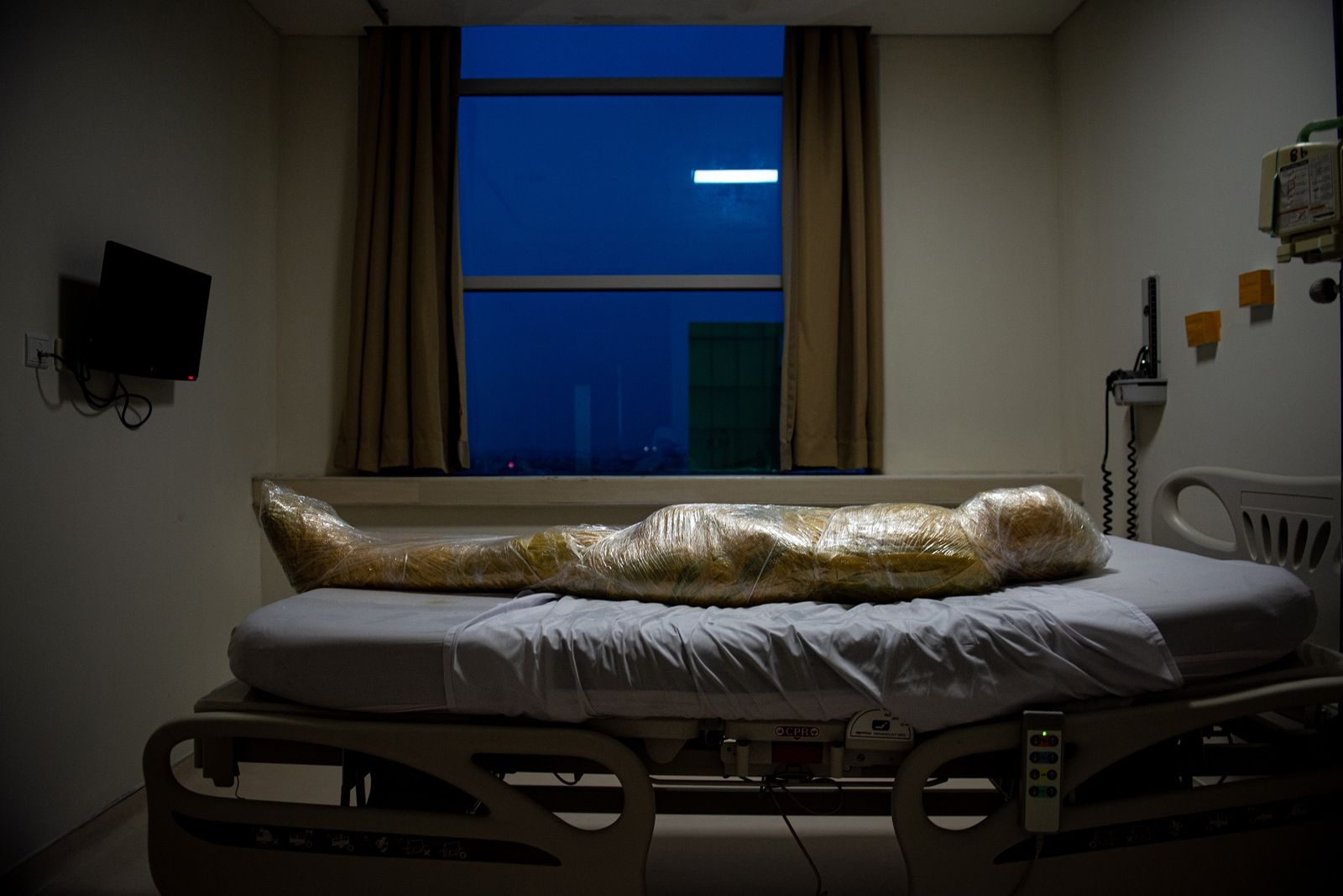 The body of a suspected covid-19 victim lies in an indonesian hospital. After the patient died, ...