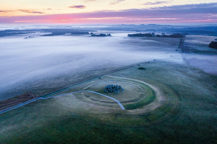 Dispersing mist reveals the great stone trilithon structures of Stonehenge. From above, the concentric rings of ...