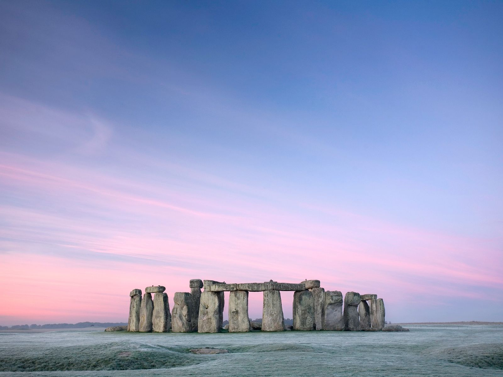 Bands of pink and purple streak the sky over Stonehenge at dawn.