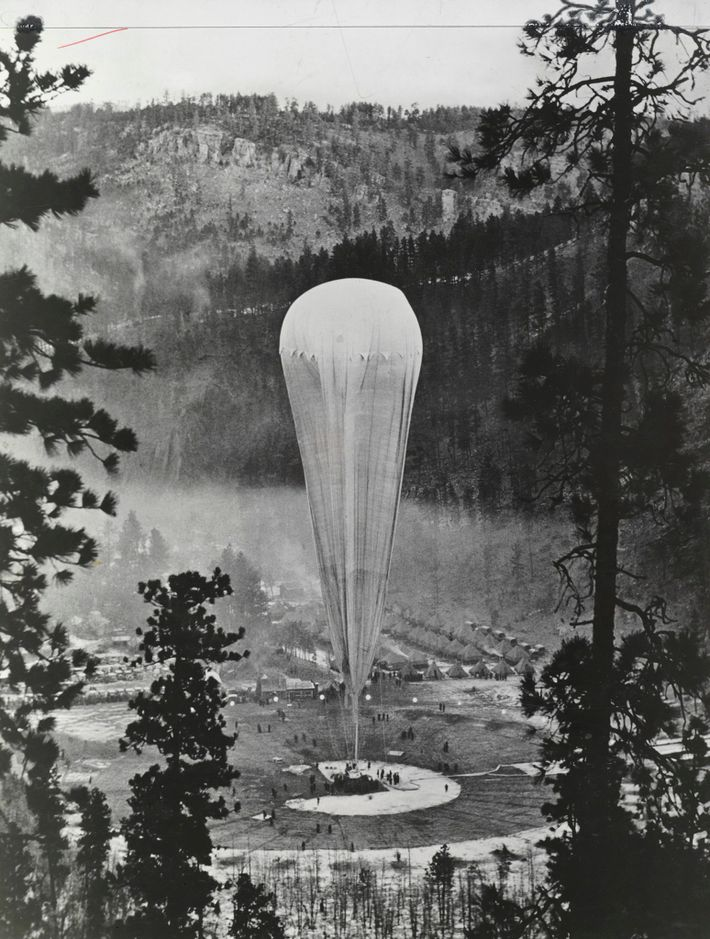 Protected by the 450-foot-high walls of the Stratobowl, the helium-filled Explorer II research balloon is inflated ...