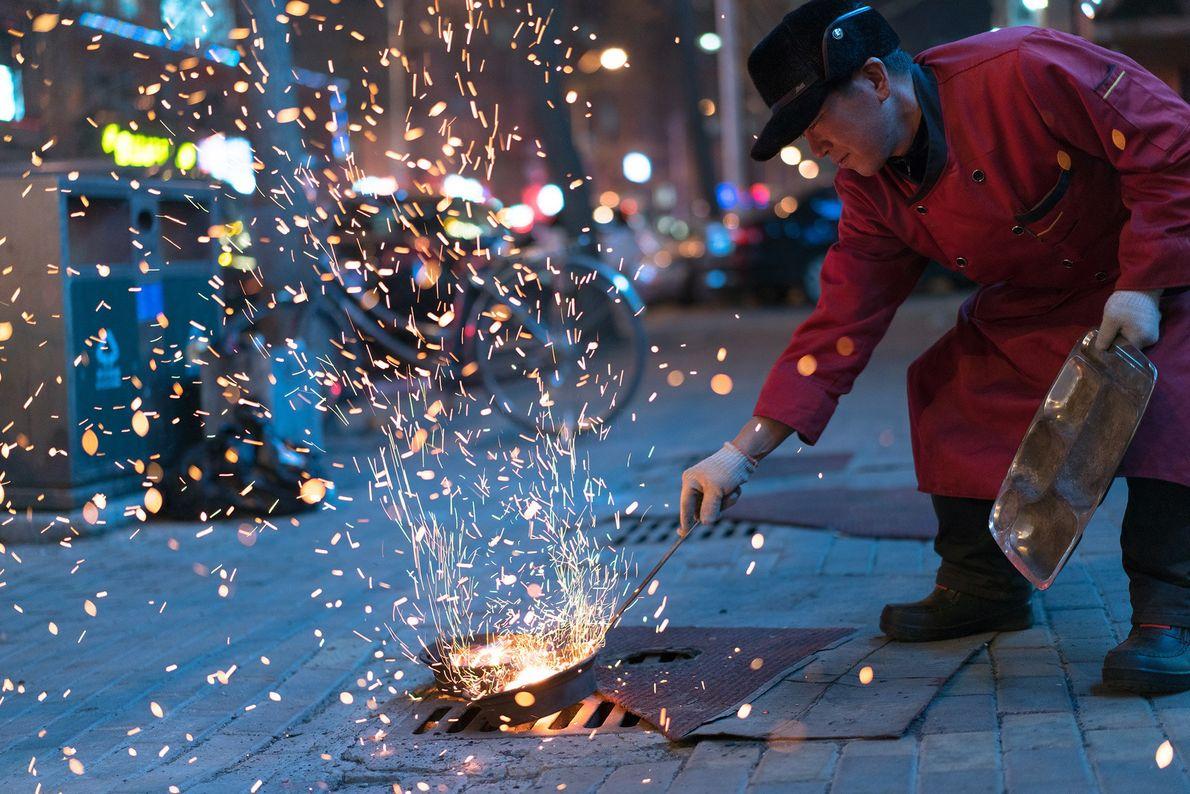 A man fans hot coals for a Korean BBQ restaurant in Dandong, China.