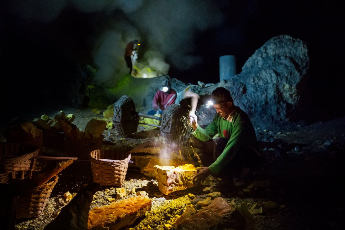 Miners break up sulphur blocks inside the volcano's crater, and fill wicker baskets to haul back ...