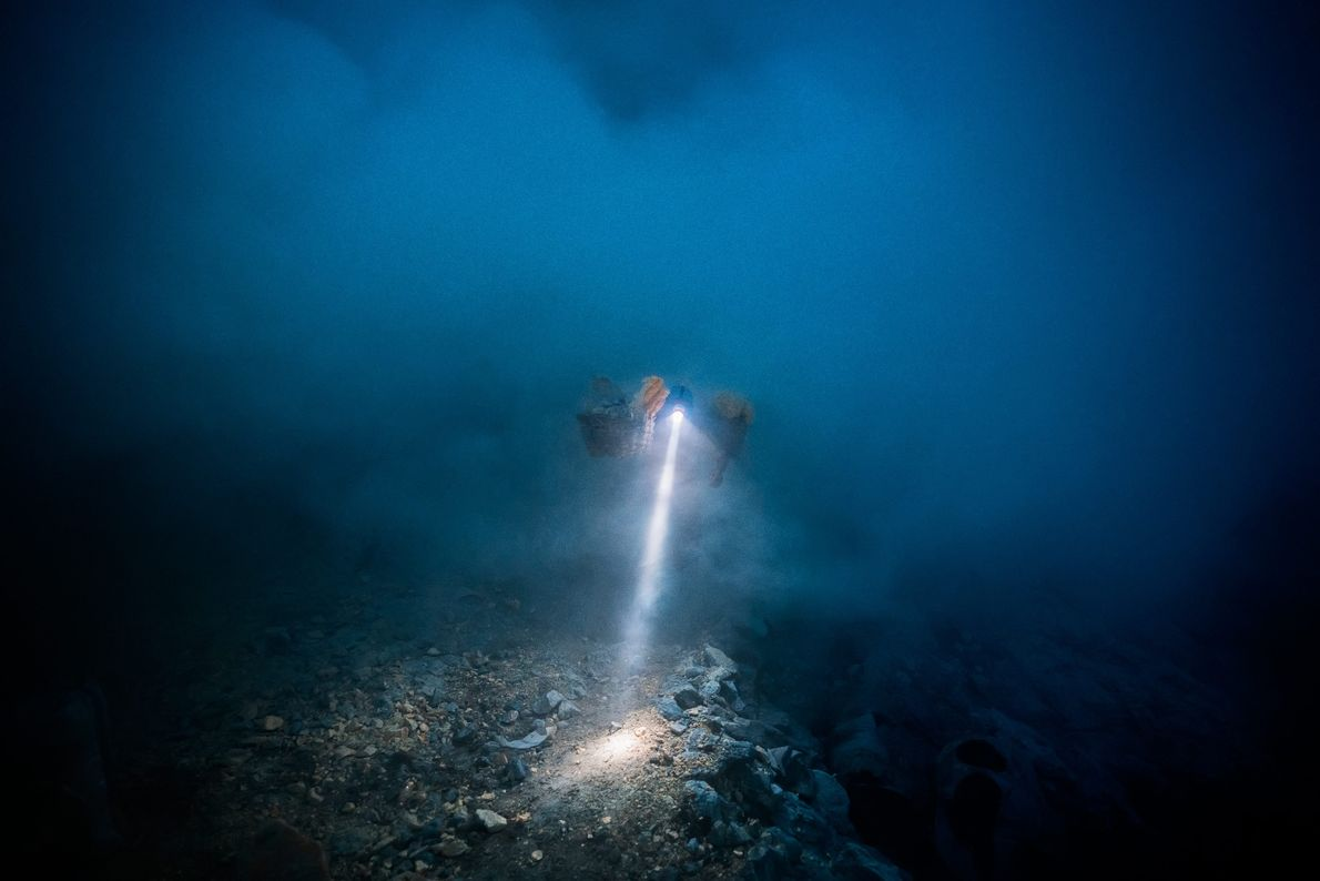 A miner's headlamp cuts through the darkness and volcanic gas. Miners often begin their work at ...