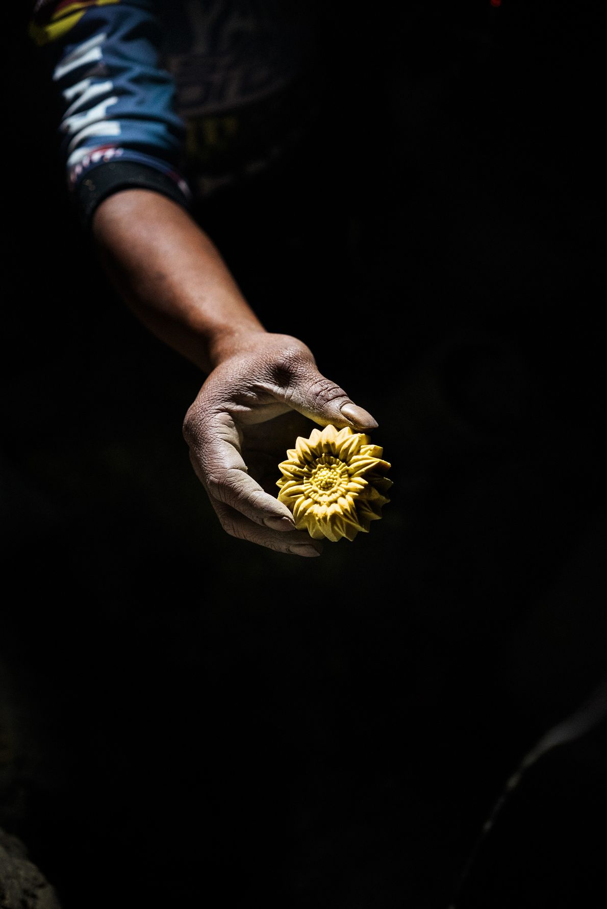 Forty-three-year-old Wito carves a flower from a block of sulphur to earn extra income from tourists.