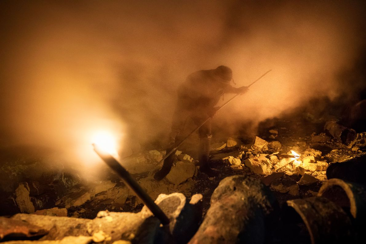 Shrouded in sulphuric gas, a miner uses a metal pole to extract lumps of sulphur.