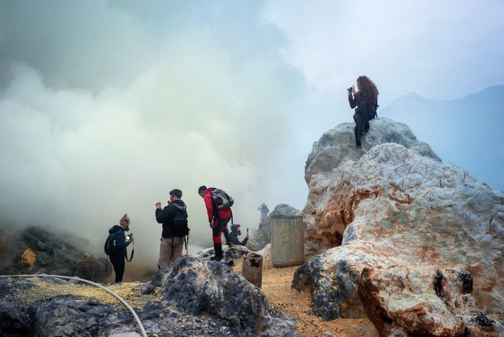 Tourists outfitted with gas masks take pictures from the shore of the crater where Kawah Ijen ...