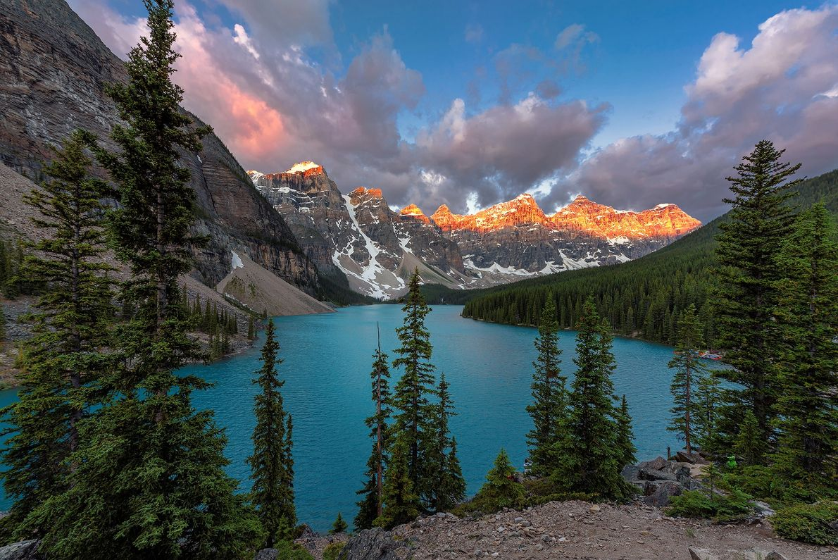 """Beautiful sunrise over turquoise waters of the Moraine Lake with red snow-covered peaks above it in ..."