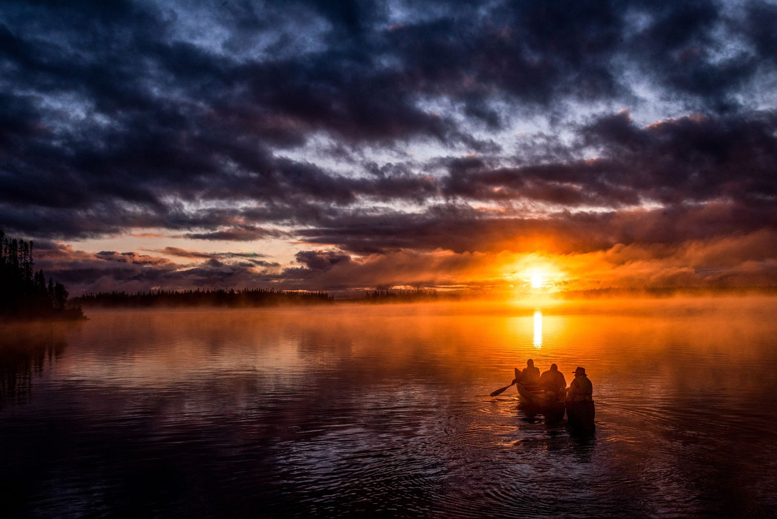 The Bossum family paddles on Lake Opemisca at sunset, Ouje-Bougoumou, Québec.