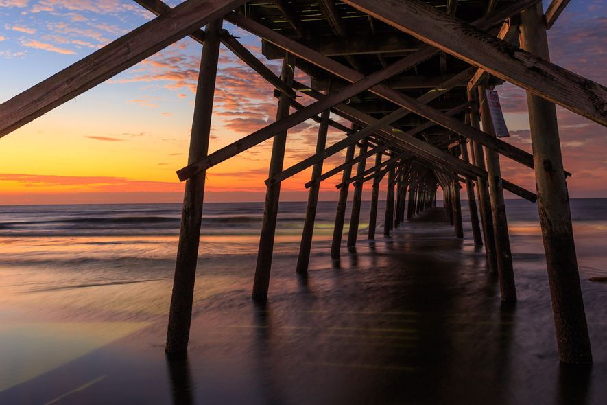Under the pier of Sunset Beach in Brunswick Island, North Carolina a sunset paints the sky ...
