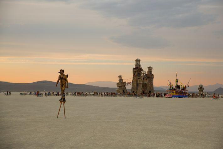 An attendee walks on stilts across the desert, leaving tall art structures behind him.