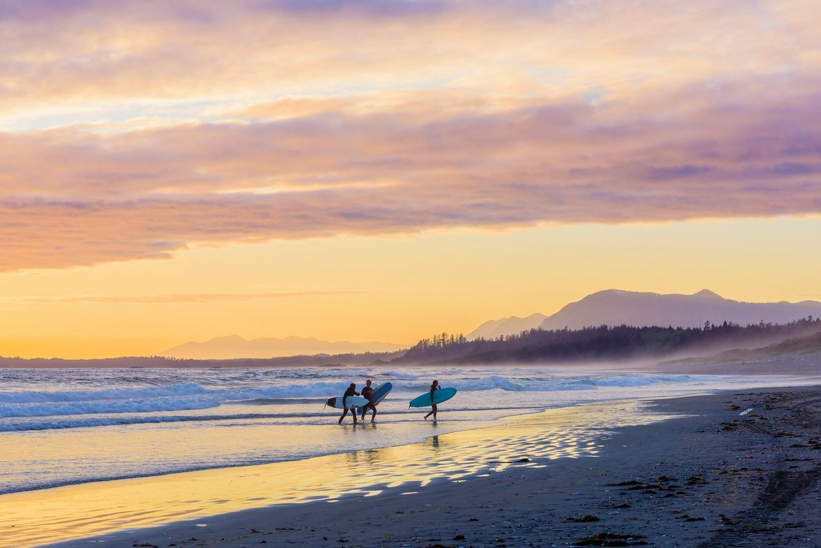 Surfers at sunset at Long Beach, Pacific Rim National Park, Vancouver Island, British Columbia.
